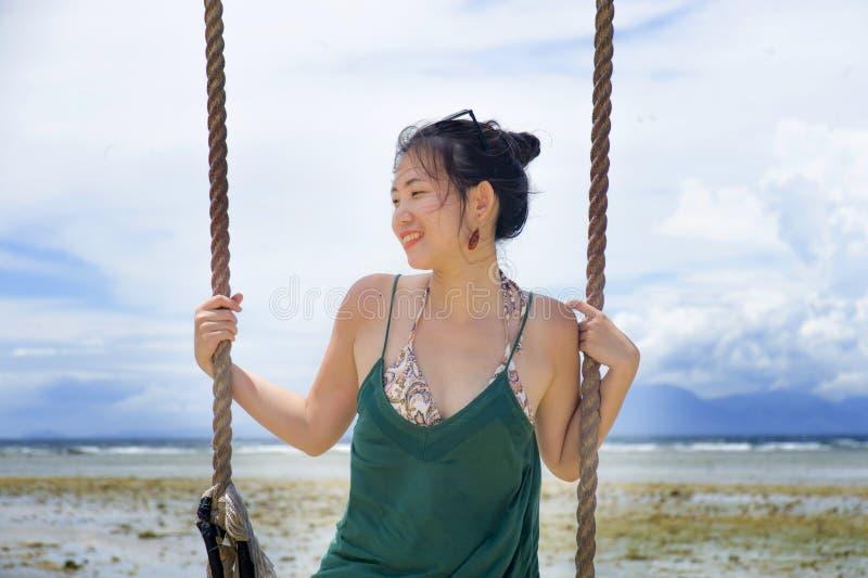 Corda chinesa asiática feliz do balanço da terra arrendada da mulher que tem o divertimento em um sorriso do céu azul do verão po foto de stock royalty free