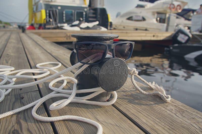 Corda da amarração no cais e nos óculos de sol imagens de stock