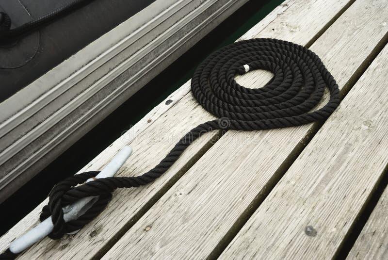 A corda de amarração rodada preta amarrou acima em um Bitt que fixa o barco ao molhe fotos de stock royalty free