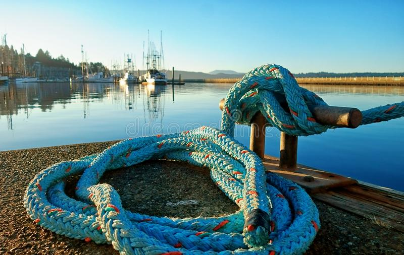 A corda de nylon azul que amarra a curva de um navio a um grampo prendeu a uma doca foto de stock royalty free