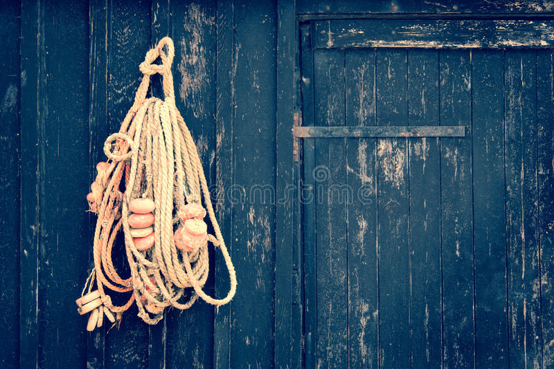 Corda del pesce che appende su una porta di legno fotografia stock