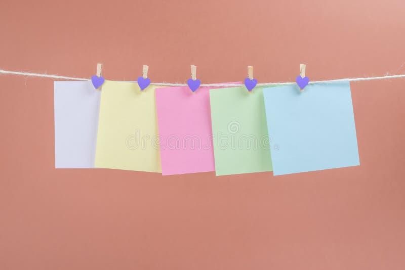 Corda di attaccatura variopinta delle carte di carta isolata su fondo marrone fotografia stock libera da diritti