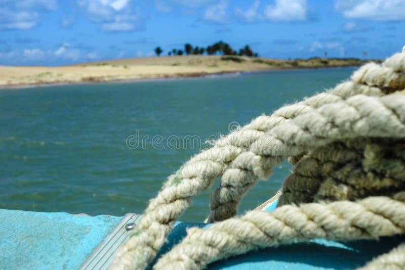 Corda di barca ed isola della sabbia su fondo fotografia stock