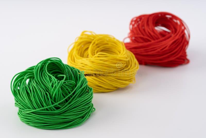 Corda, corda di gomma variopinta Corda torta meravigliosamente su un fondo bianco fotografia stock libera da diritti