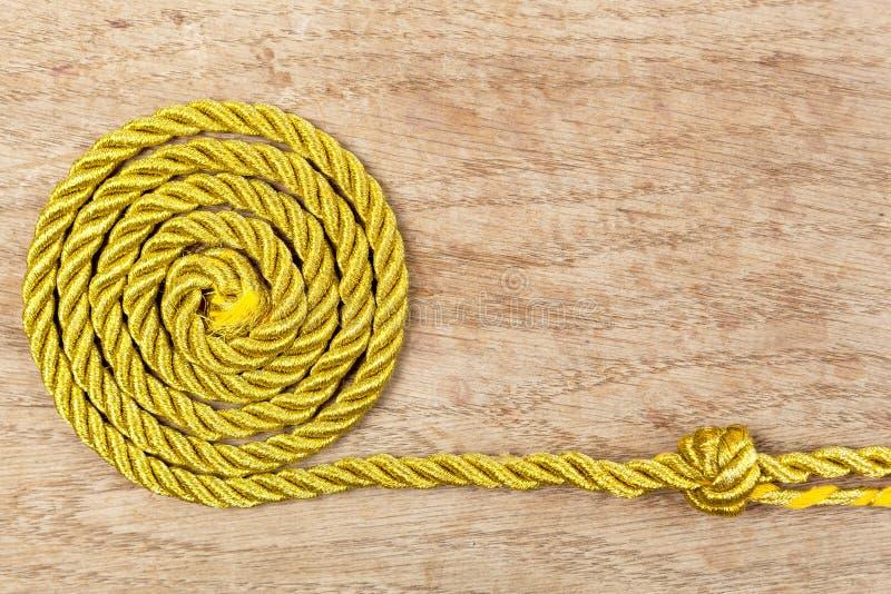 Corda dorata su fondo di legno immagini stock