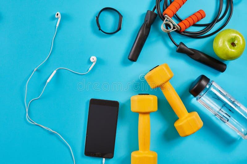 Corda dos pesos, do telefone celular e de salto no fundo azul Vista superior Aptidão, esporte e conceito saudável do estilo de vi foto de stock royalty free