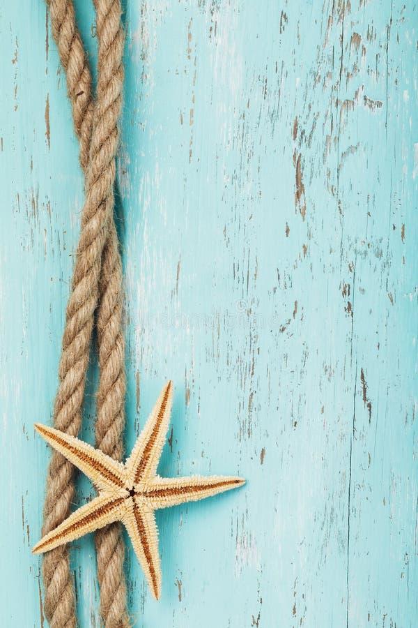 Corda e stelle marine sui precedenti di un bordo di legno anziano immagini stock libere da diritti
