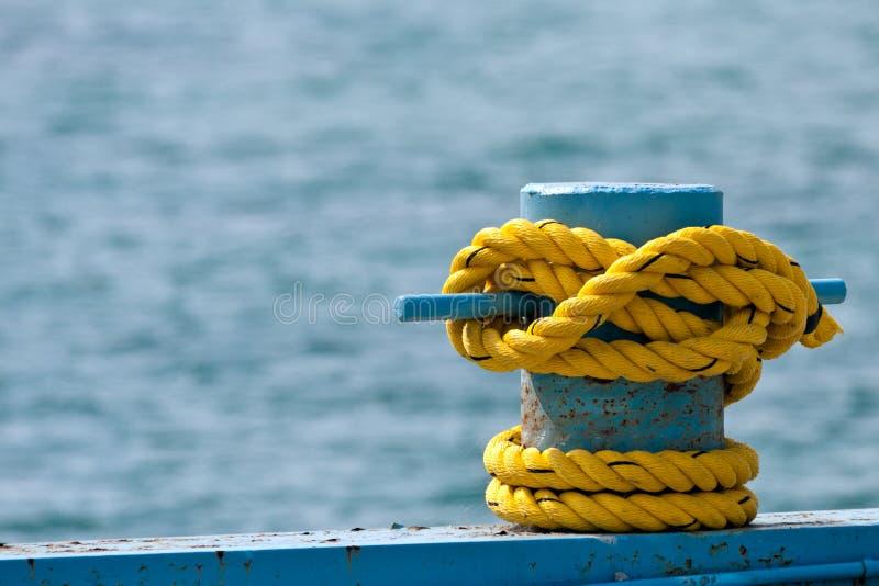 Corda gialla sulla colonna di ormeggio fotografie stock