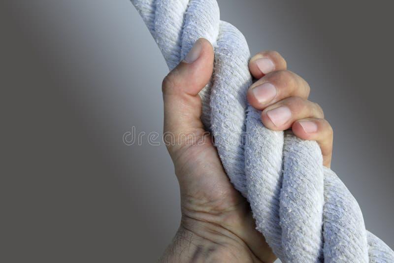 Corda invecchiata della pinsa della gru a benna della mano dell'uomo forte grande immagini stock
