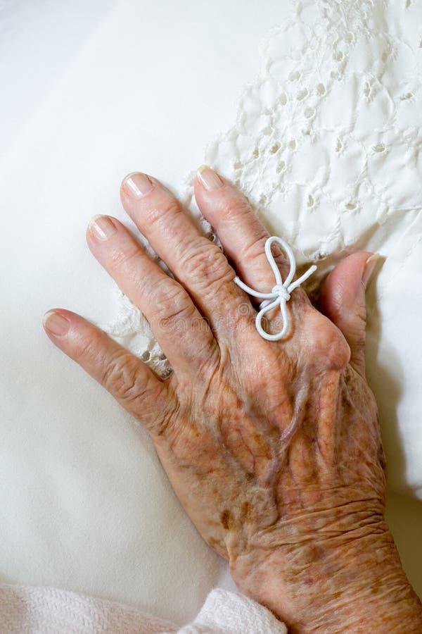 Corda legata sul dito della donna anziana immagini stock