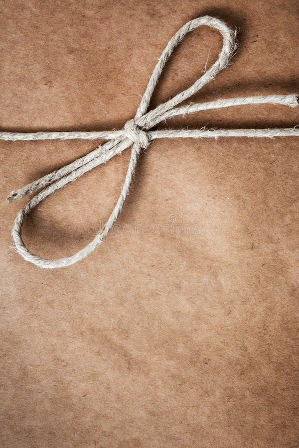 Corda legata in un arco, sopra la carta marrone del pacchetto fotografia stock libera da diritti