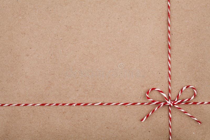 Corda ou guita do Natal amarrada em uma curva no contexto do papel de embalagem fotos de stock