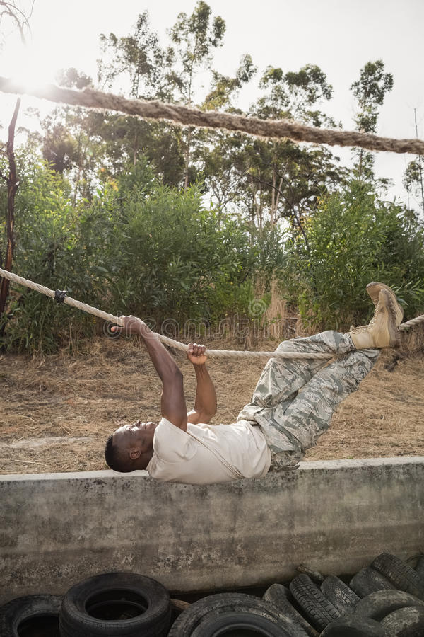 Corda praticando do soldado militar novo que escala durante o curso de obstáculo fotos de stock