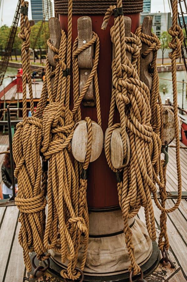 Corda rolada e polias apoiadas no mastro central de um navio de navigação em um dia nebuloso em Amsterdão imagens de stock