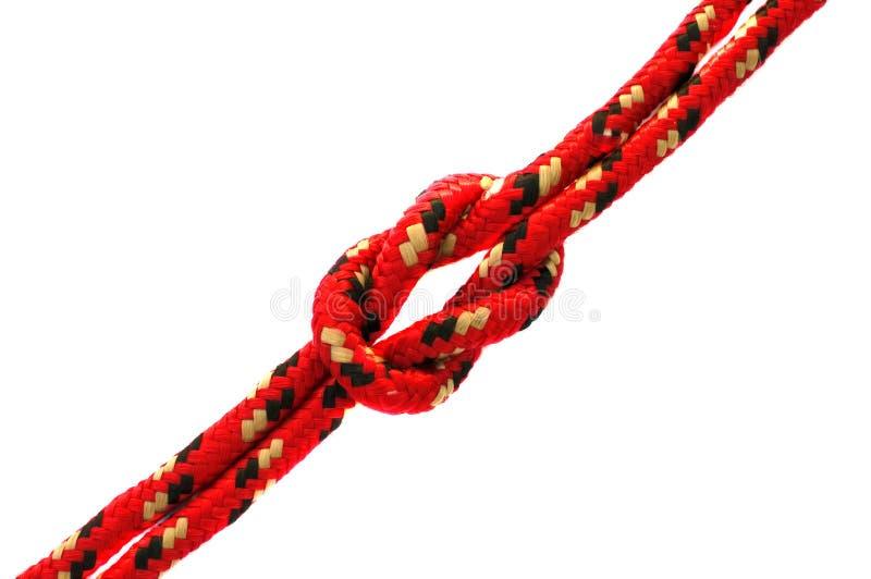 Corda rossa con un nodo immagine stock