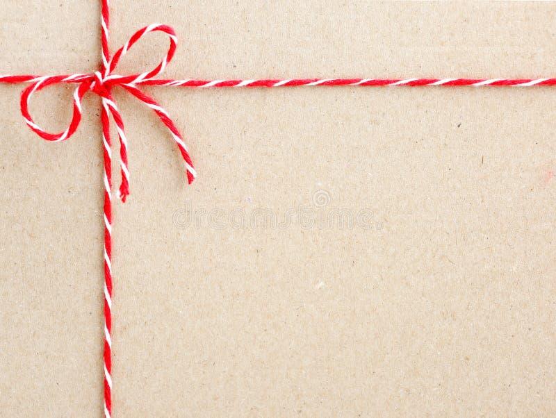 Corda vermelha da guita amarrada em uma curva no contexto de papel imagens de stock