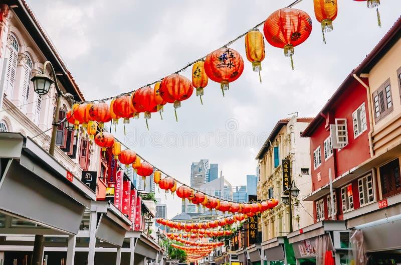 Cordas das lanternas chinesas vermelhas amarradas através de uma rua de casas tradicionais da loja ao arrumador no ano novo chinê fotografia de stock royalty free