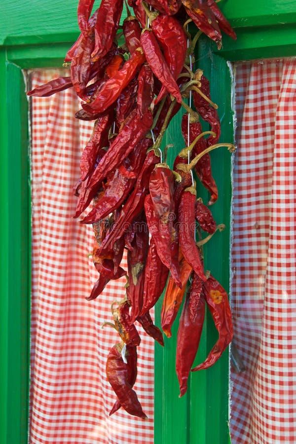 Cordas das pimentas de pimentão que penduram fora da janela na vila na Croácia imagens de stock