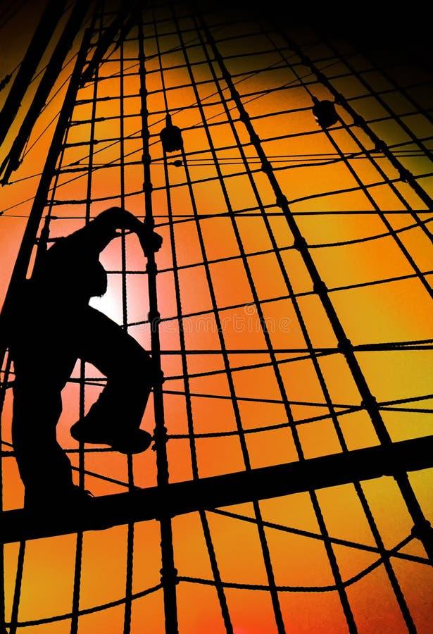 CORDAS DE ESCALADA DO NAVIO DA SILHUETA DO HOMEM DO MARINHEIRO CONTRA O CÉU DO POR DO SOL DO OURO foto de stock royalty free