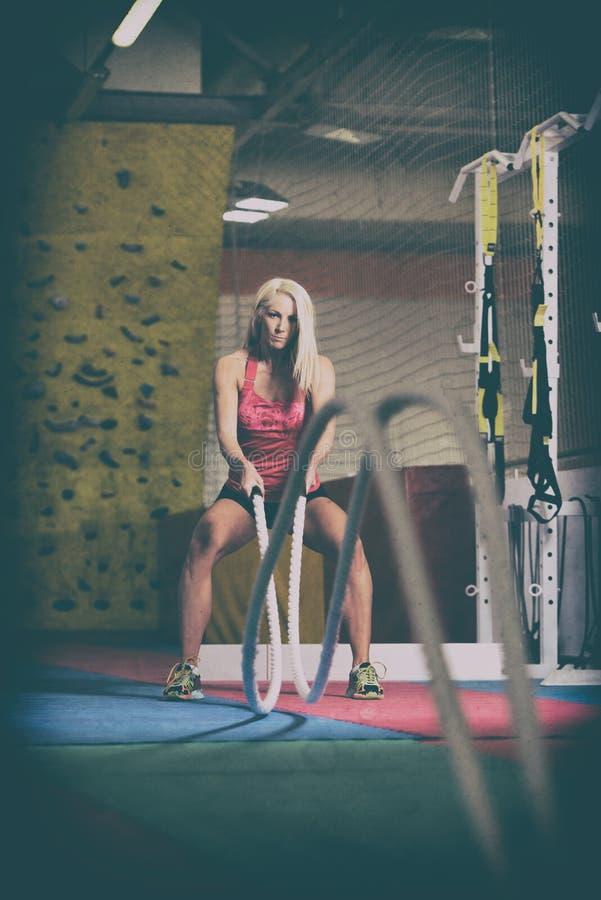 Cordas de luta da jovem mulher no exercício do exercício do Gym fotos de stock royalty free