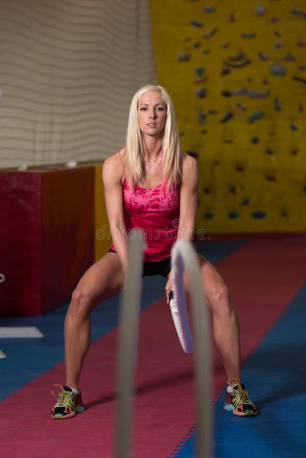 Cordas de luta da jovem mulher no exercício do exercício do Gym imagens de stock