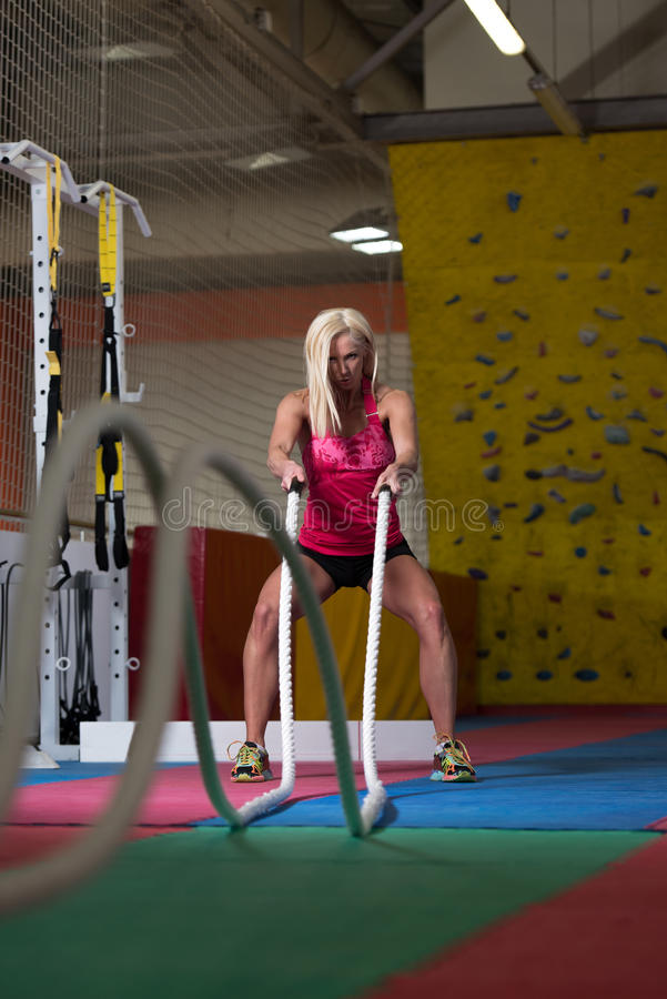 Cordas de luta da mulher da aptidão no exercício do exercício do Gym fotografia de stock