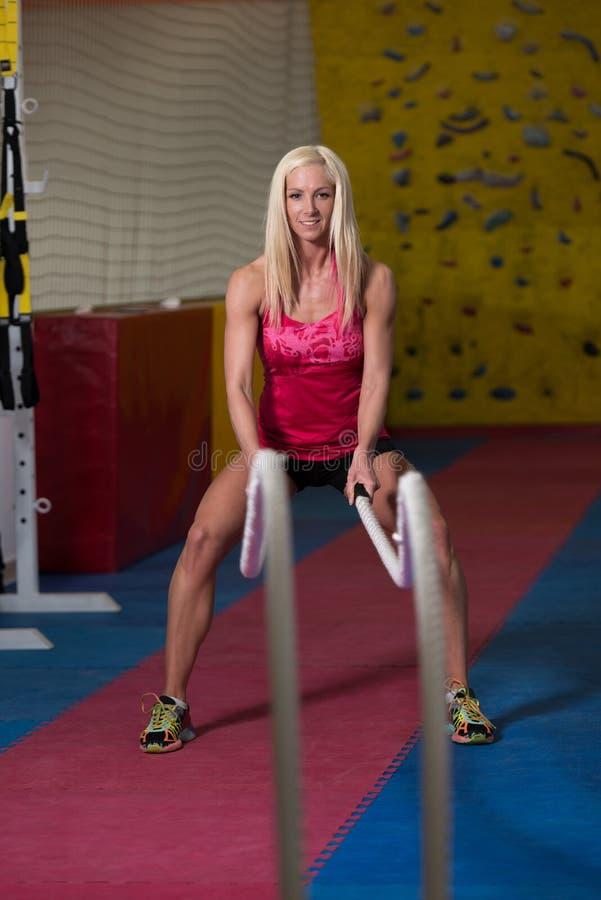 Cordas de luta da mulher da aptidão no exercício do exercício do Gym fotos de stock