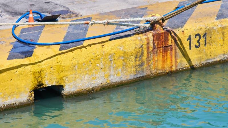 Cordas de Rusty Harbor Bollard With Ship em um cais pintado amarelo imagens de stock