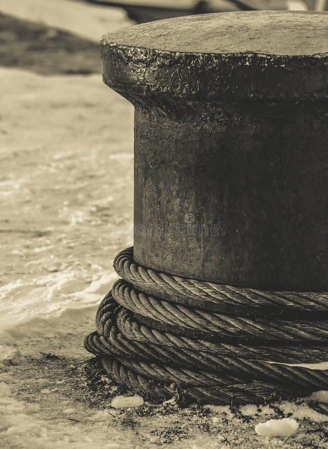 Cordas em um poste de amarração com neve no fundo fotografia de stock