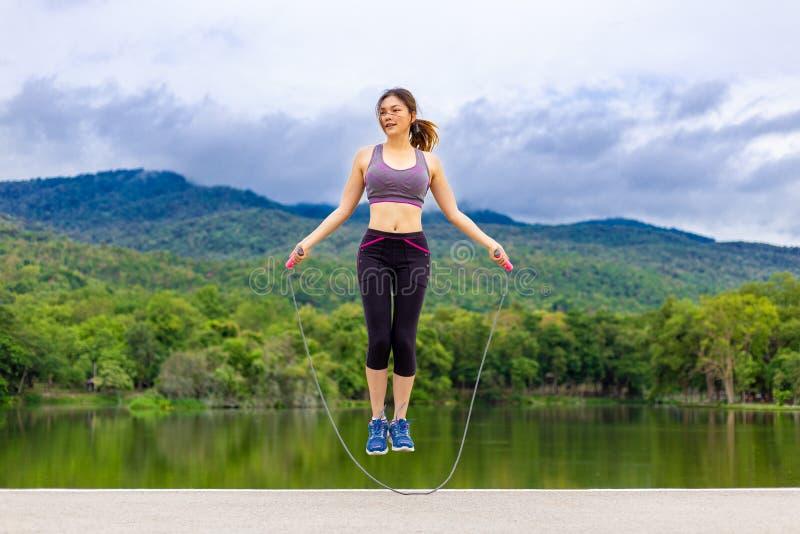 Corde à sauter de belle jeune femme asiatique heureuse pendant son exercice de matin à un lac avec le fond de montagnes image libre de droits