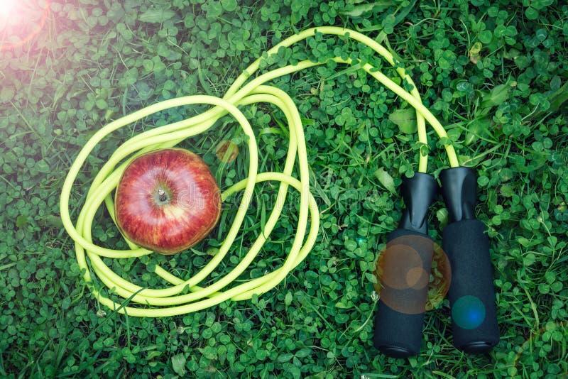 Corde à sauter et pomme rouge image stock