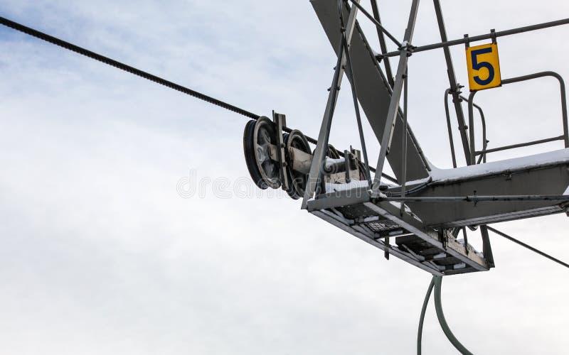 Corde d'acciaio sopra le ruote nel meccanismo sopra la colonna di sostegno dell'ascensore di sci, numero 5 sul piatto giallo Ampi fotografie stock