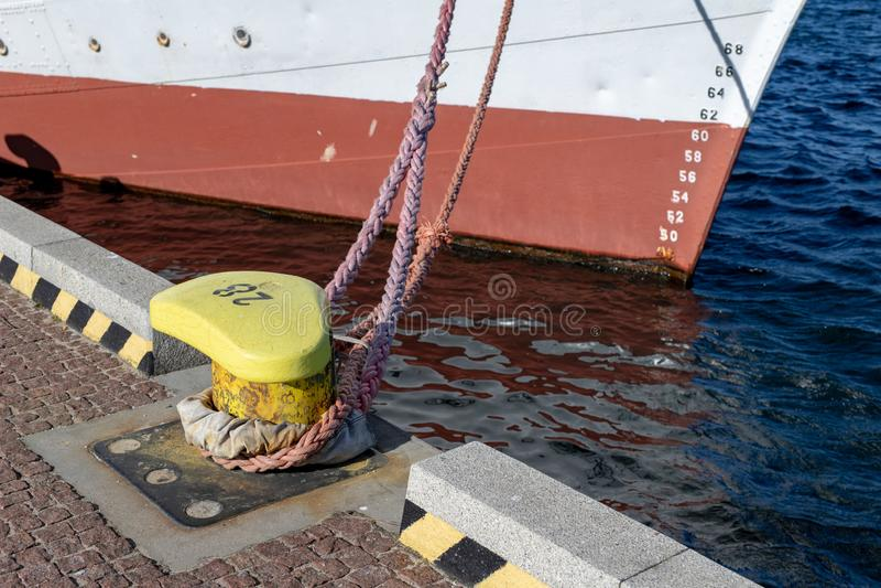 Corde d'amarrage de bateau amarrée sur la borne Bateau amarré dans le port images libres de droits