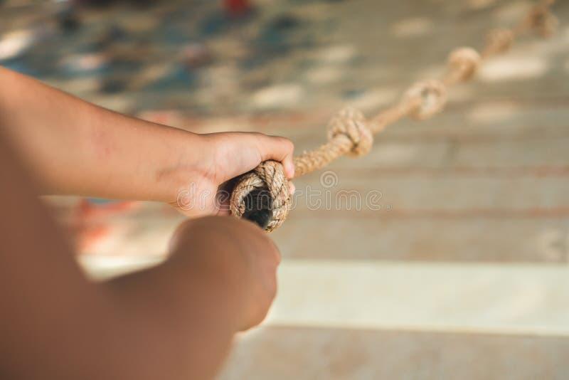 Corde de participation de main d'enfant tout en escaladant un mur en bois photos stock