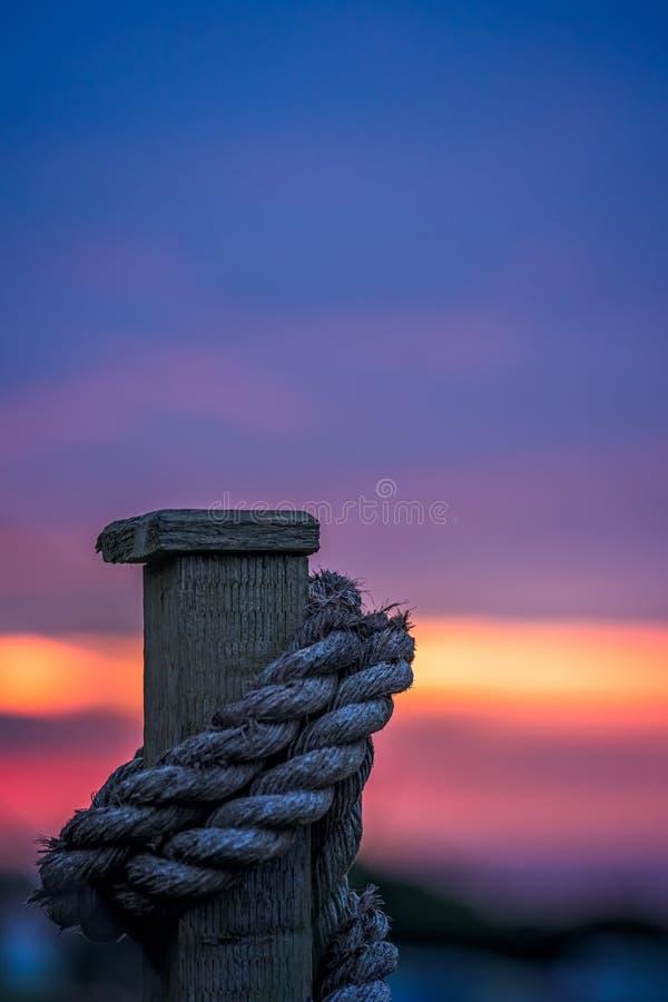 Corde en bois de barrière et ciel cornouaillais de coucher du soleil photo stock