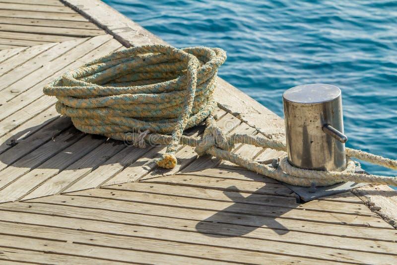 Corde et borne d'amarrage sur l'eau de mer et le fond de yachts photos stock