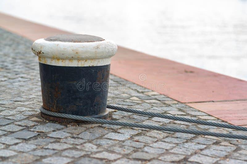 Corde et borne d'amarrage sur le lac contre la rivière photos stock
