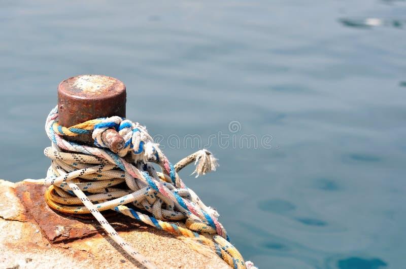Corde marine sur la borne d'amarrage dans le port photo libre de droits