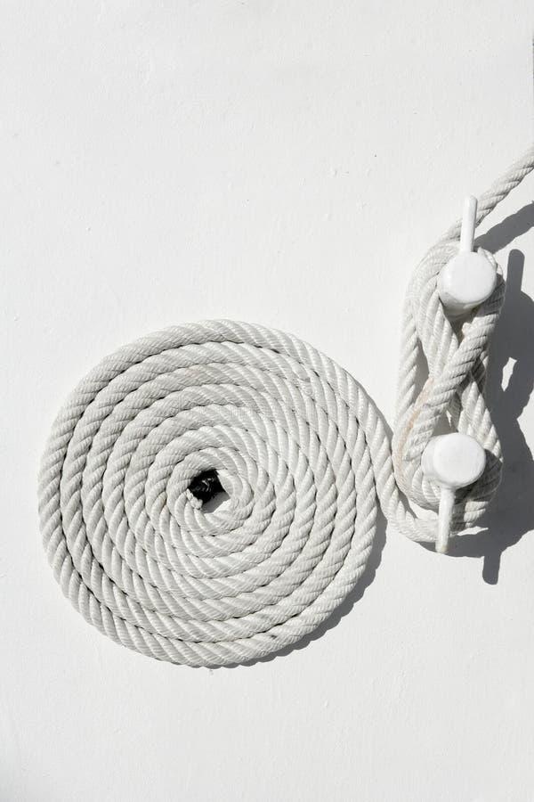 Corde nautique spiralée de mer blanche sur l'amarrage de bateau photos stock