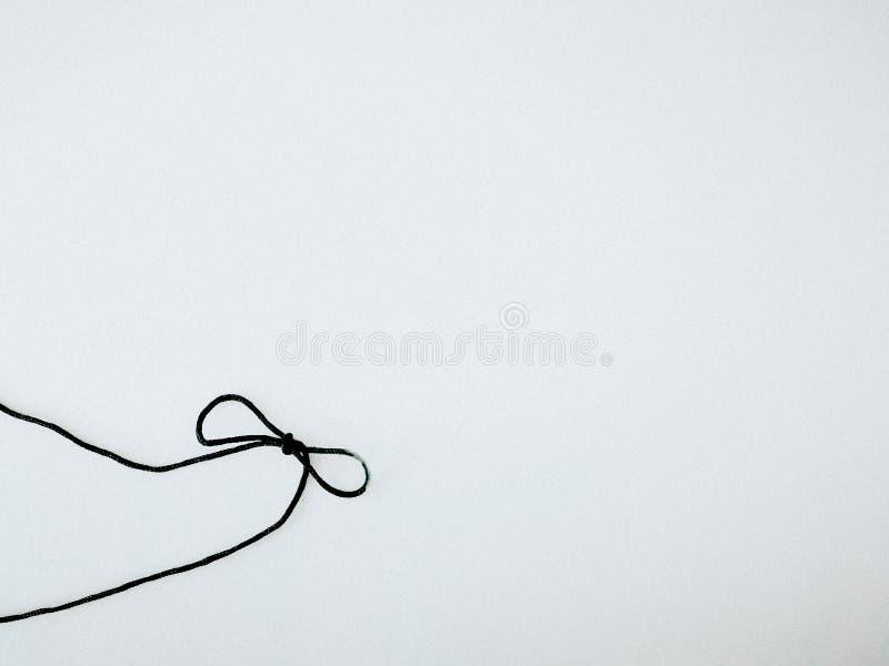 Corde noire avec le lien de ruban sur le fond blanc photographie stock libre de droits