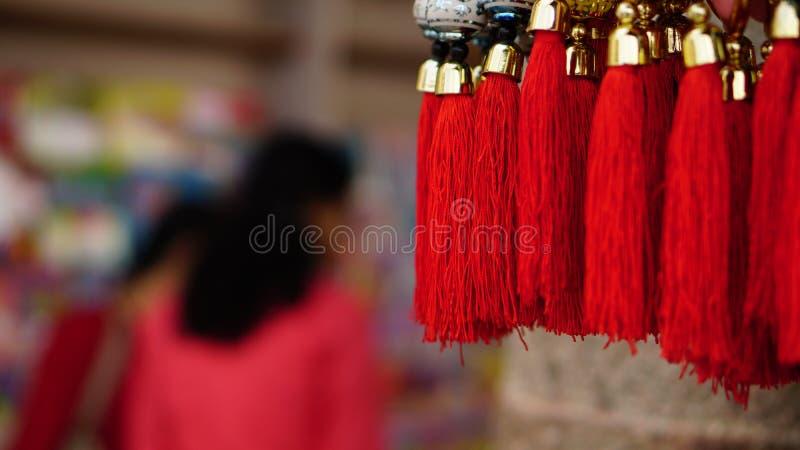 Corde rosse di buona fortuna di Buddist con acquisto di signora nel fondo immagine stock