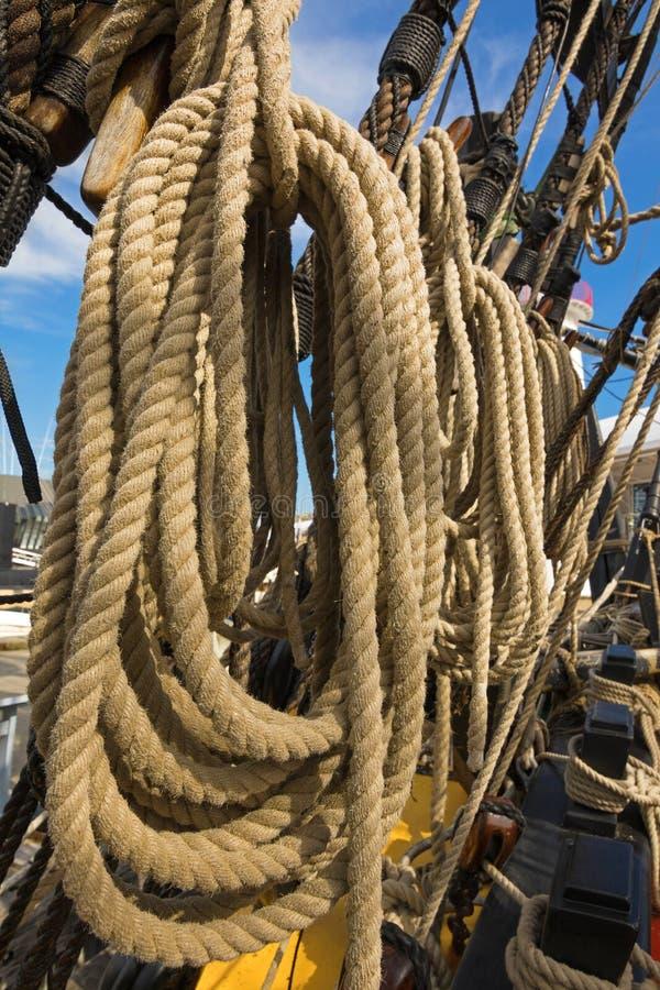 Corde spesse rotolate sulla vecchia nave vicino ai morsetti di legno immagini stock libere da diritti