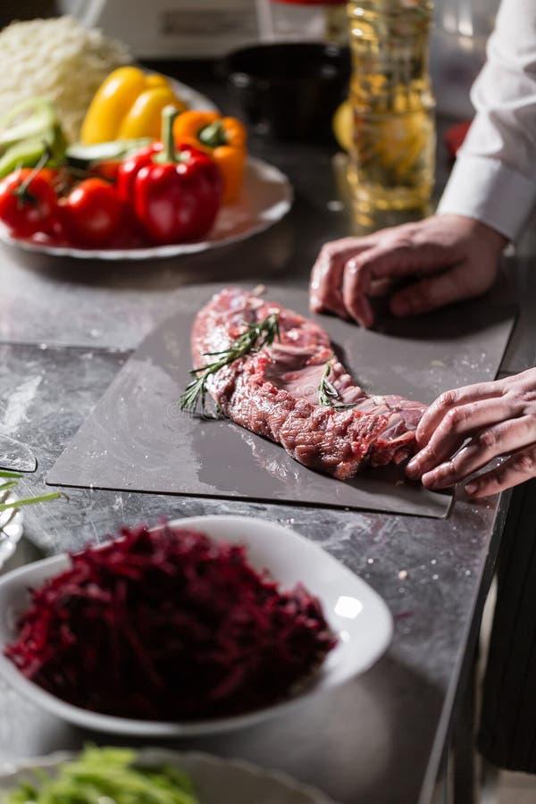 Cordeiros raros prontos para a marinada com alecrins Cozimento com fogo na frigideira Cozinheiro chefe profissional em uma cozinh foto de stock