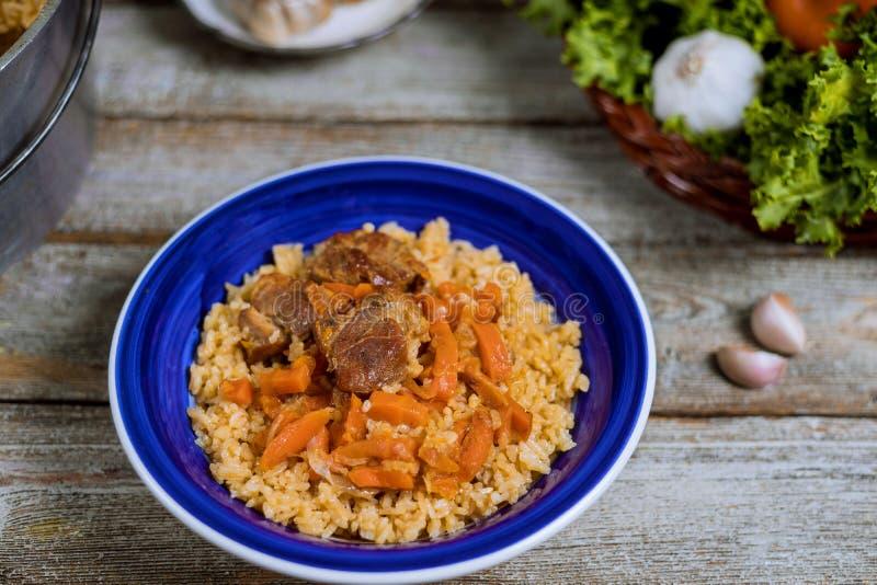 Cordero del pilaf de Samarkand, arroz, cebolla, zanahorias amarillas, tabla vegetal de las especias en plato nacional del Uzbek fotografía de archivo