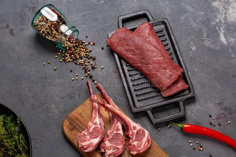Cordero fresco crudo de la carne en las especias Chesno y Rosemary del hueso en un fondo negro imagen de archivo