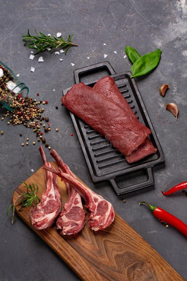 Cordero fresco crudo de la carne en las especias Chesno y Rosemary del hueso en un fondo negro foto de archivo libre de regalías