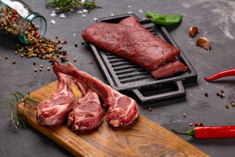 Cordero fresco crudo de la carne en las especias Chesno y Rosemary del hueso en un fondo negro fotos de archivo libres de regalías