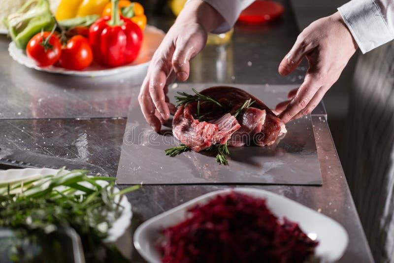 Corderos raros listos para el adobo con romero El cocinar con el fuego en sartén Cocinero profesional en una cocina de fotografía de archivo libre de regalías