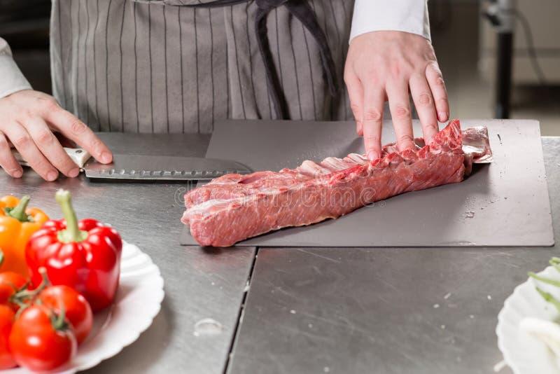 Corderos raros listos para el adobo con romero El cocinar con el fuego en sartén Cocinero profesional en una cocina de fotos de archivo
