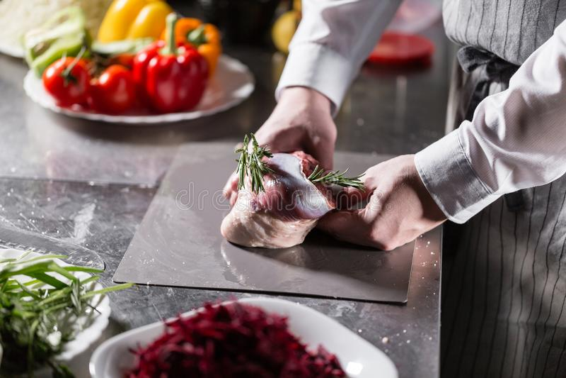Corderos raros listos para el adobo con romero El cocinar con el fuego en sartén Cocinero profesional en una cocina de fotos de archivo libres de regalías